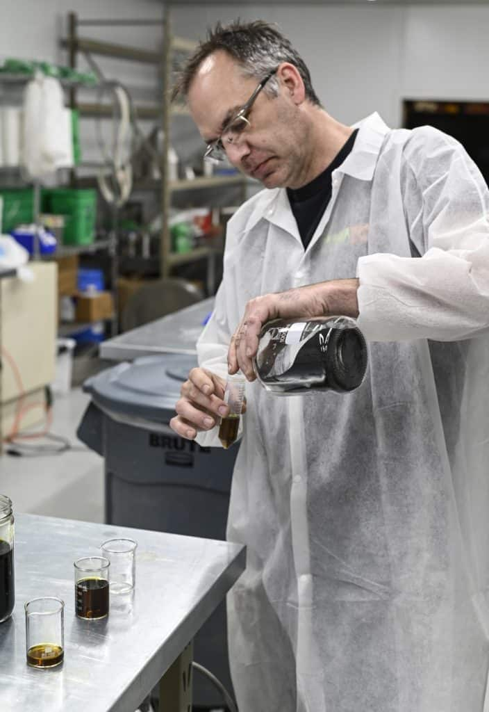 man measuring chemicals in lab gear